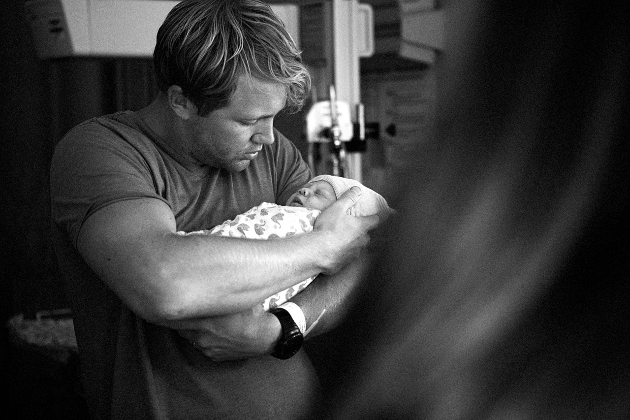 black and white ,birth photograph of a father holding his new daighter.