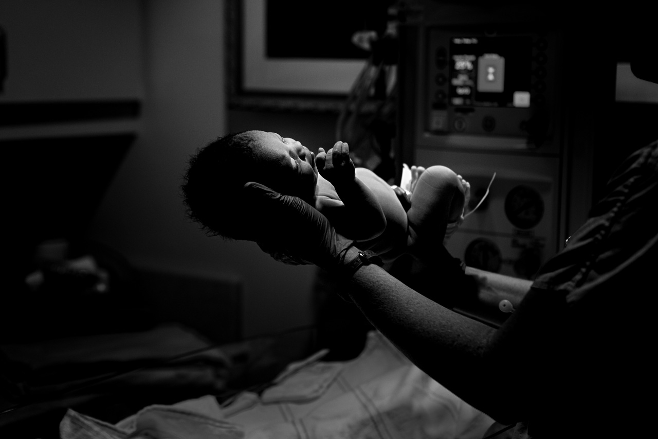 A newborn baby is held by a doctor