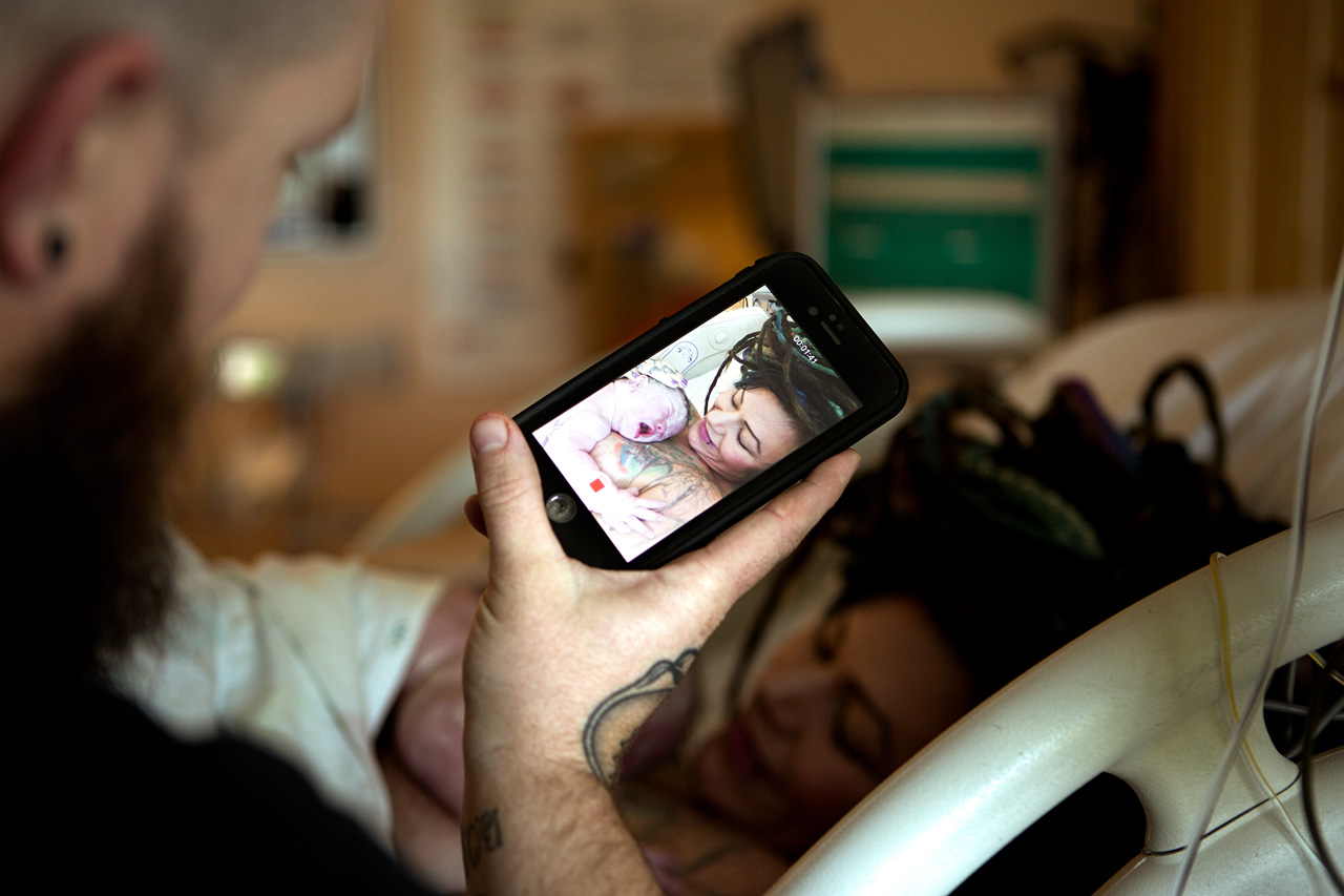 birth photography postpartum image os a father taking a picture of his wife and daughter after delivery.