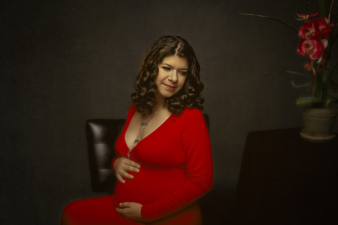 color portrait of a mother to be dressed in a red gown.