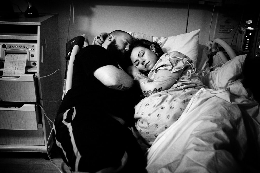 black and white birth photography photo by Leona Darnell of a husband and wife napping during labor at Kaiser Permanente