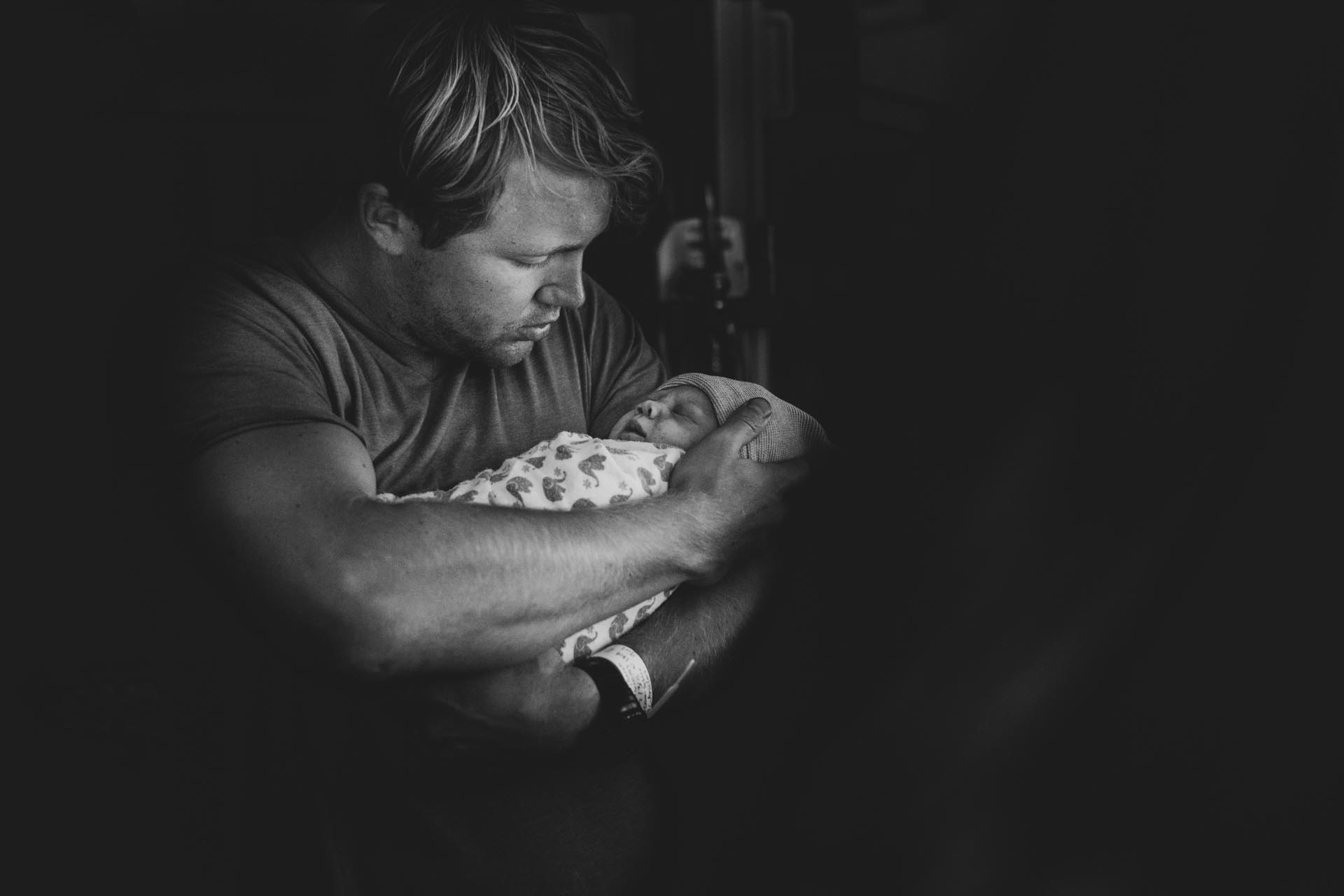 Los Angeles birth photography black and white birth photography photo of a Pasadena dad holding his daughter for the first time.