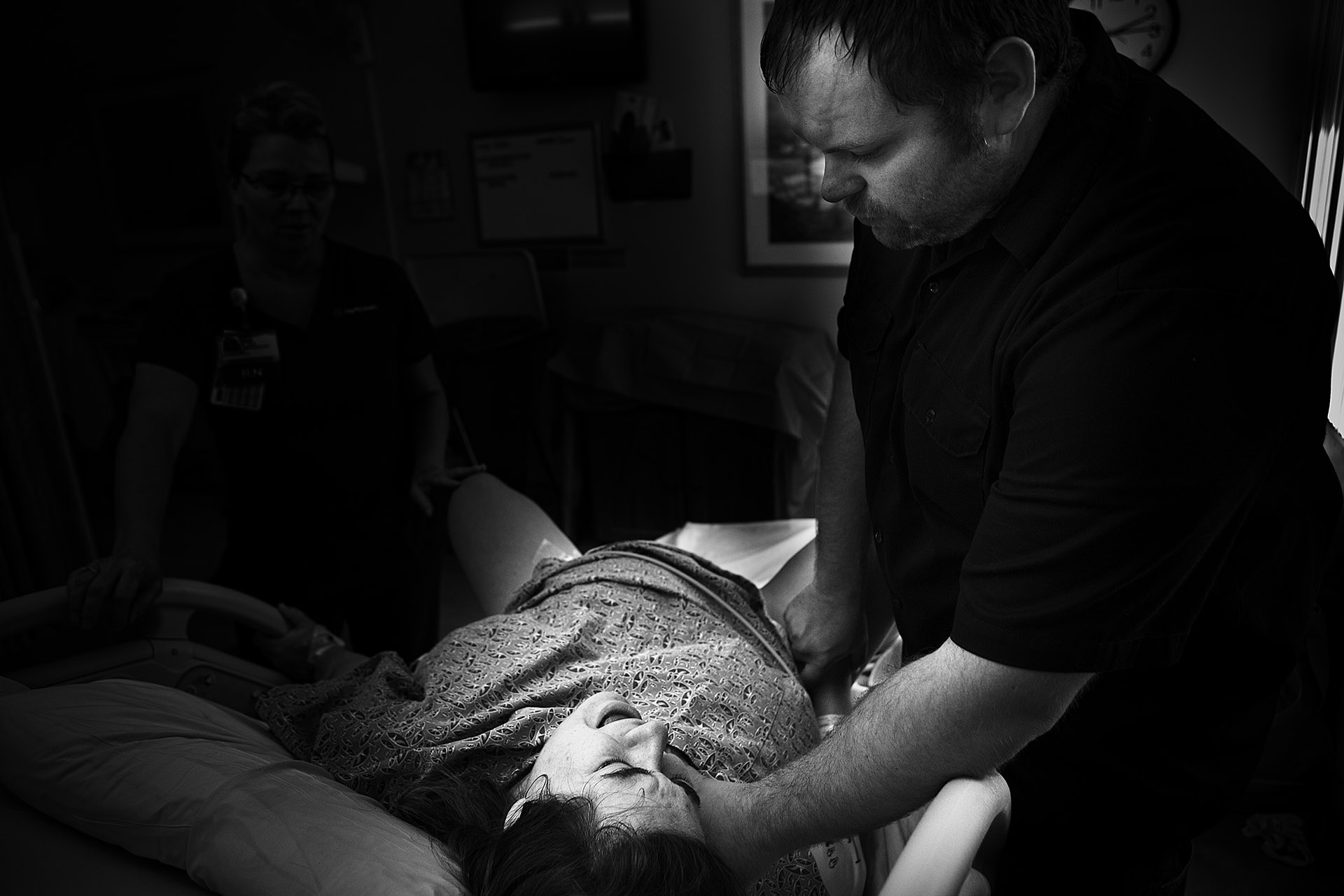 Black and White image of a laboring mother in pain being supported by her partner.