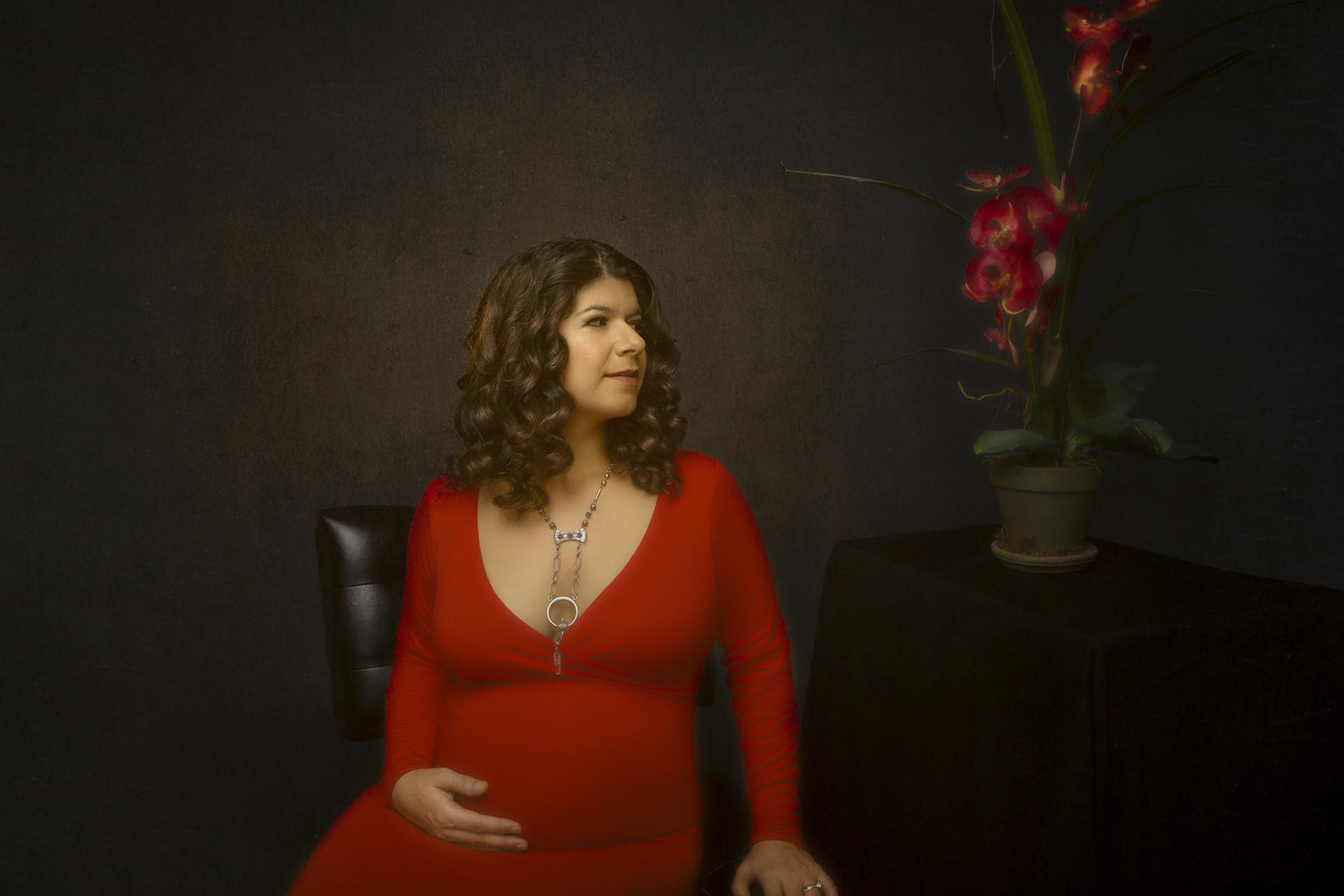 Color maternity portrait of a woman wearing a red maternity dress