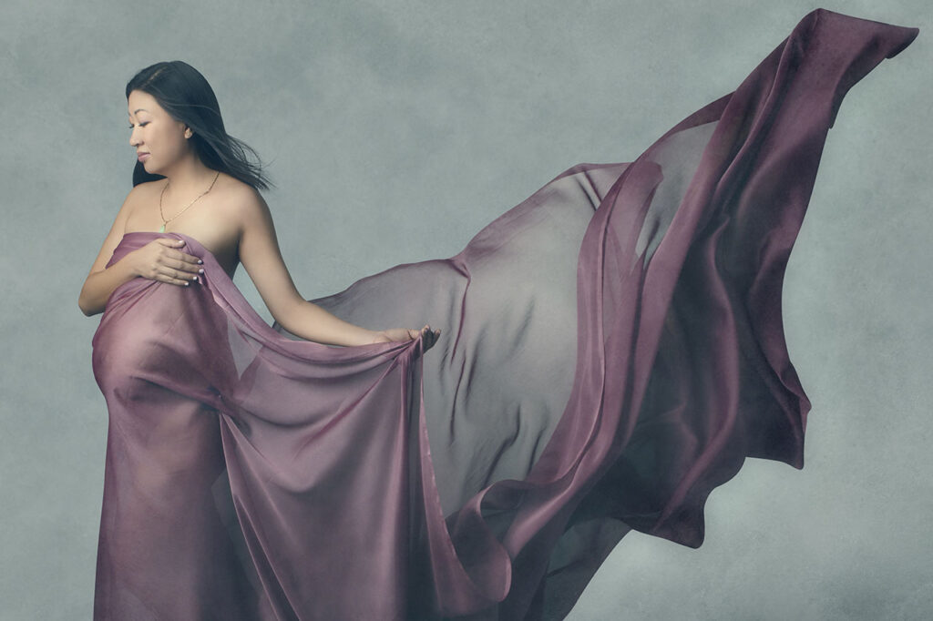 Los Angeles maternity photographer, Leona Darnell, shows an Asian woman with chiffon draped around her