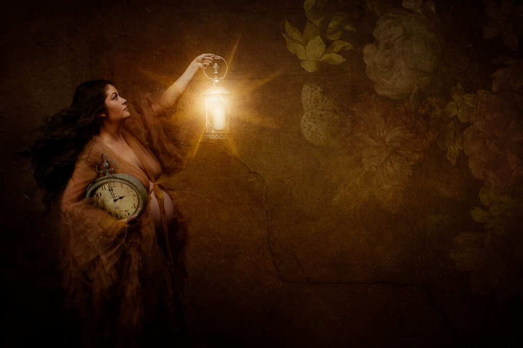 Fine Art Maternity portrait of a woman in a flowing brown tulle robe holding a lantern of light