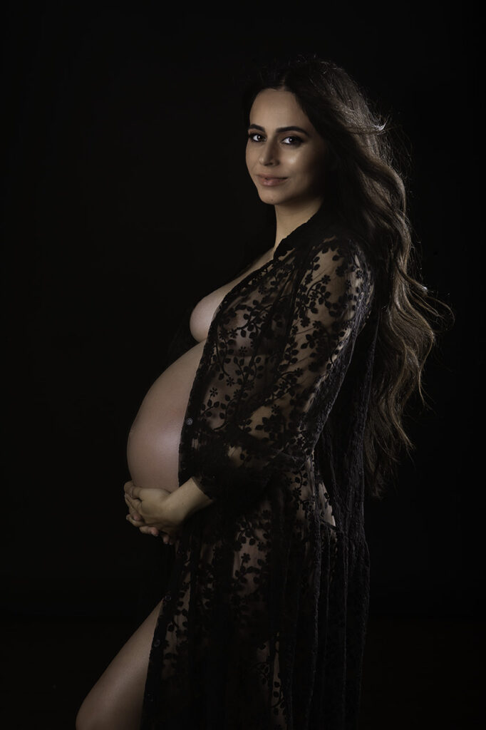 Los Angeles maternity photographer, Leona Darnell shows a mother in a lace black robe with her hair flowing and lit.