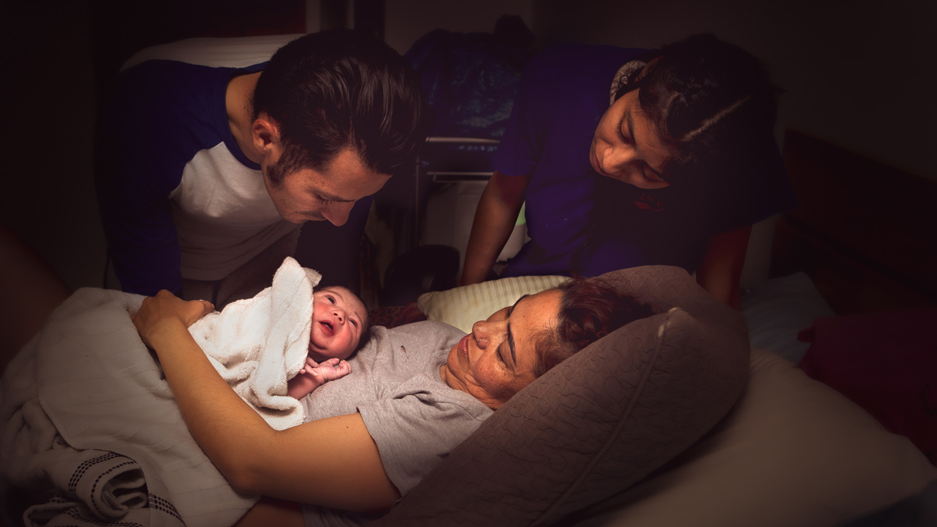 Los Angeles home birth photo by Leona Darnell showing a family looking at a newborn