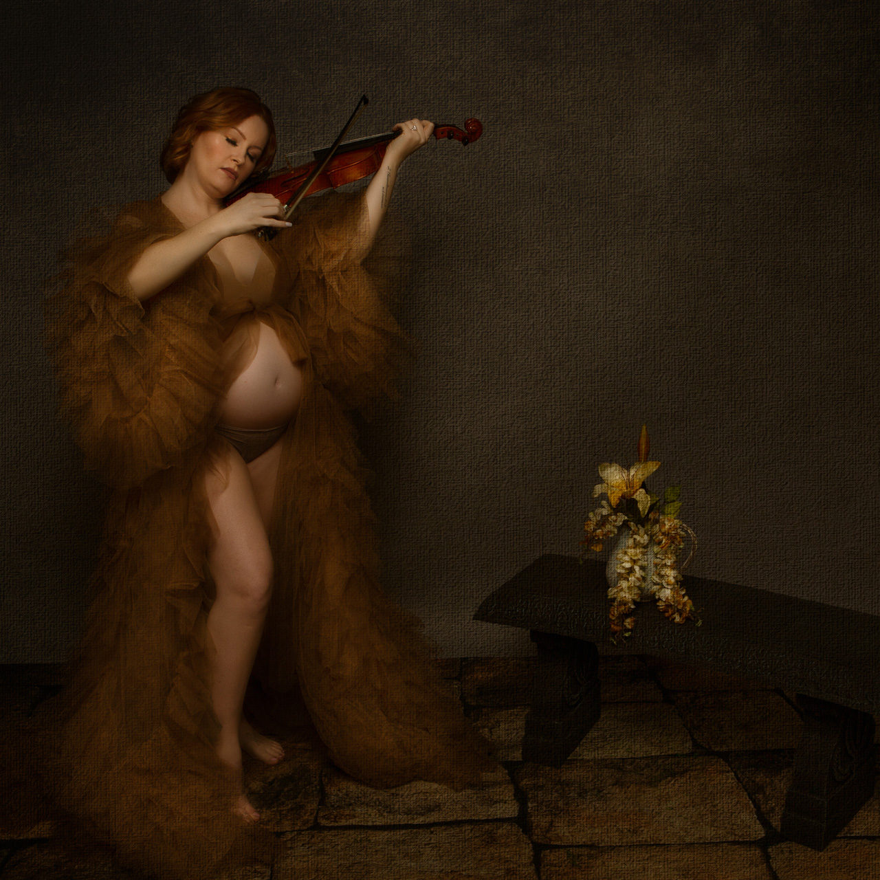 Beautiful maternity portrait by Leona Darnell showing a mother to be in a tulle robe playing the violin.