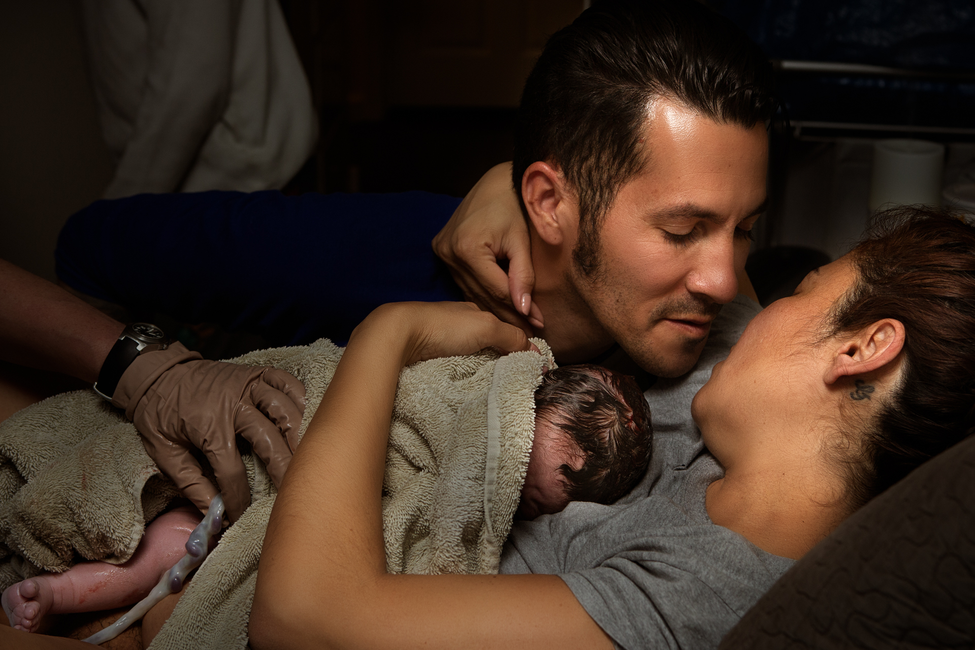 Color birth photo by Leona Darnell showing a mother and father right after birth kissing