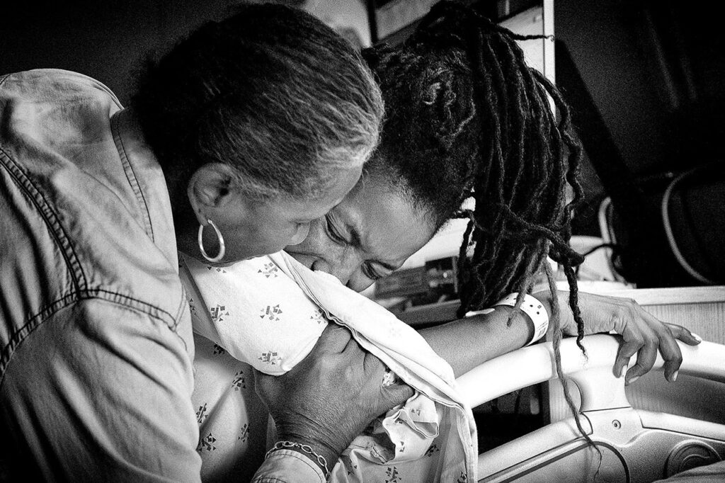 black and white image of a mother helping her daughter through labor by UCLA birth photographer, Leona Darnell