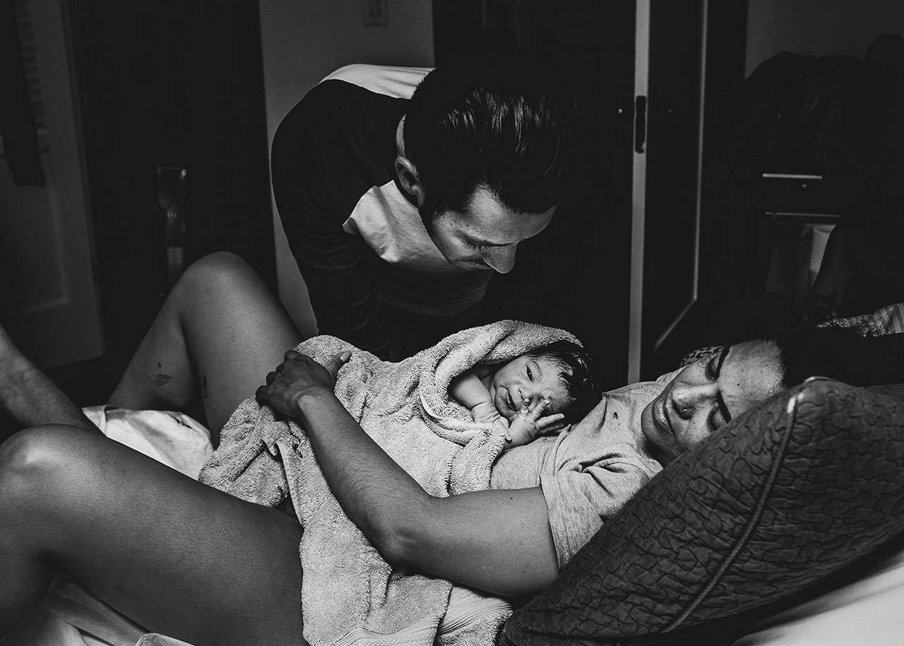 postpartum birth photo of a father looking at his newborn during a los angeles home birth.