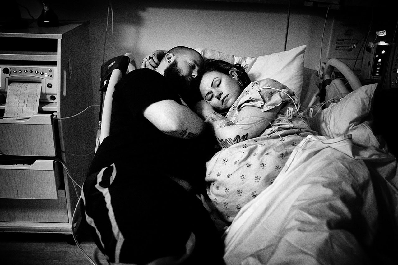 black and white image of a couple sleeping between contractions by Los Angeles birth photographer, Leona Darnell