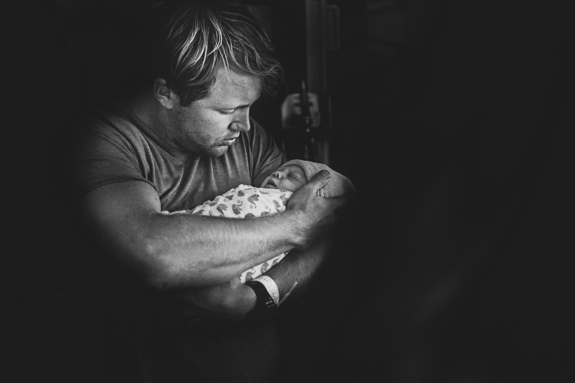 black and white birth photo of a dad holding his newborn daughter by Cedars Sinai birth photographer, Leona Darnell.