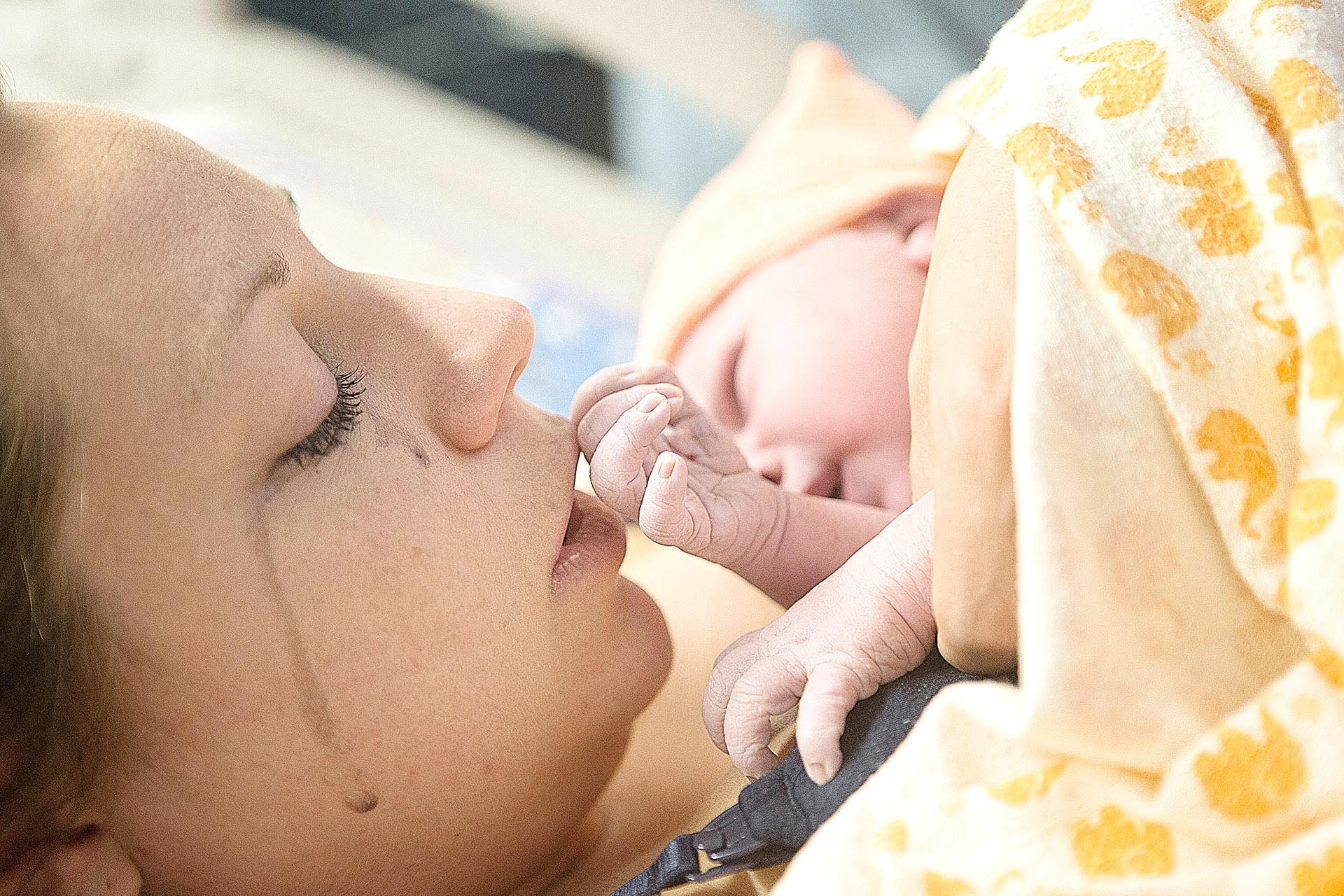 birth photo of a mom kissing her daughters hand by los angeles birth photographer, Leona Darnell