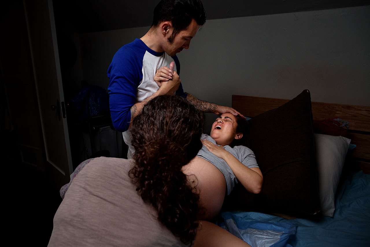 Color photo of a homebirth. Mom is laboring hard with the support of her partner by Santa Monica birth photographer, Leona Darnell.