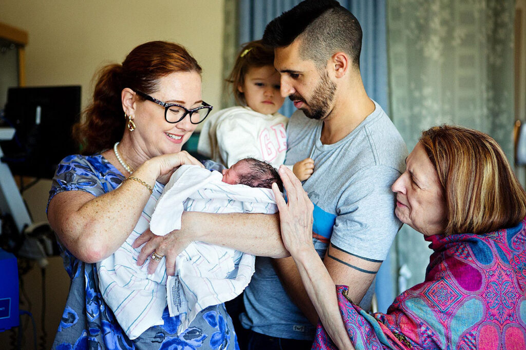 color postpartum photo of a family meeting a newborn baby by Leona Darnell, Glendale birth photographer and doula.