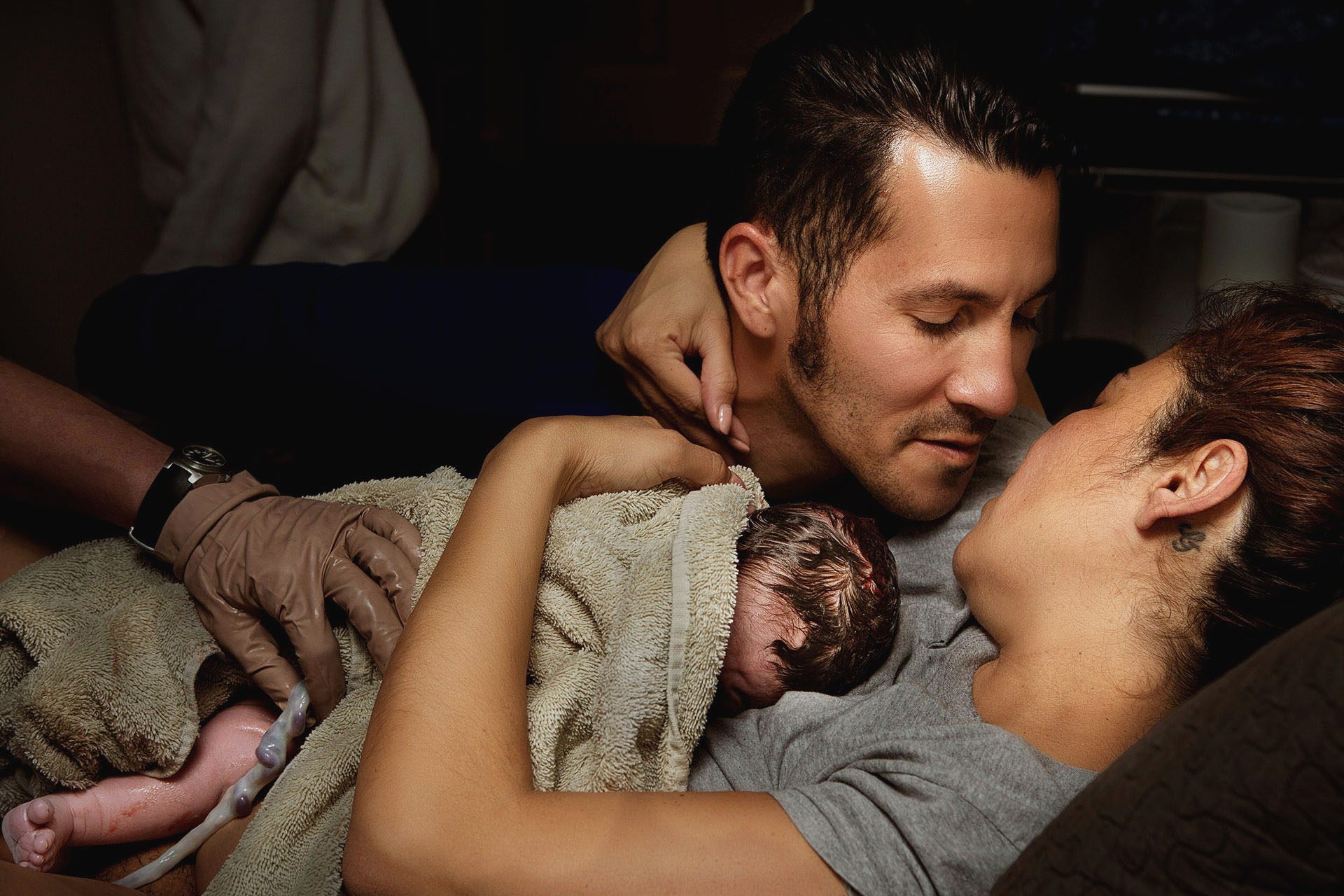 postpartum birth photo of parents embacing after the birth of their child by Los Angeles birth photographer Leona Darnell